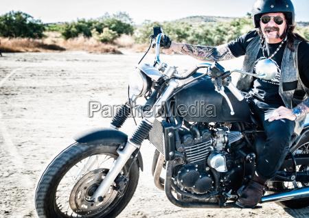 portrait of male motorcyclist on arid