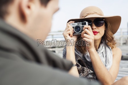young woman photographing boyfriend on coastal