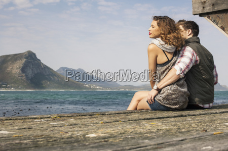 young couple sitting on edge of