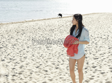 young woman strolling on beach holding