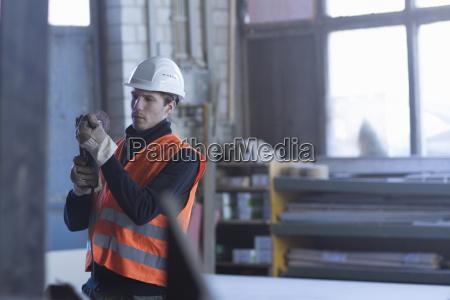 werksarbeiter prueft bauteil in betonbewehrungsfabrik