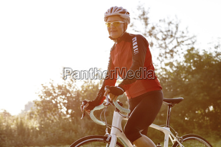 mature cyclist riding past forest