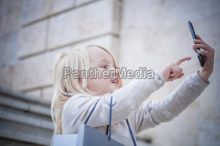 young girl on stairway using touchscreen