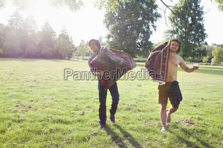 two young men carrying rugs for