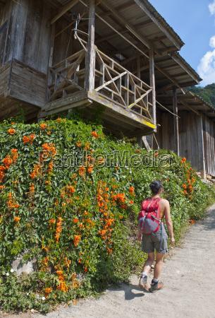female tourist walking up village street