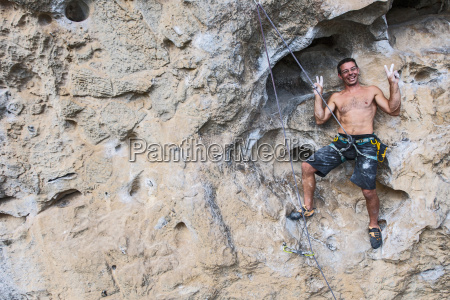 rock climber standing on rock face