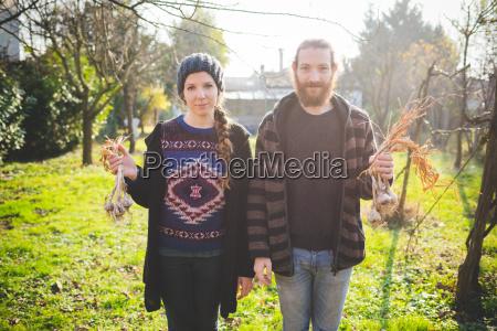 couple standing in garden holding fresh