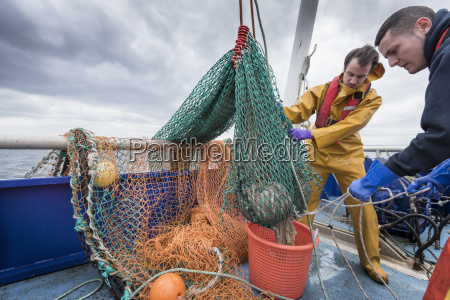 fishermen and research scientist landing catch