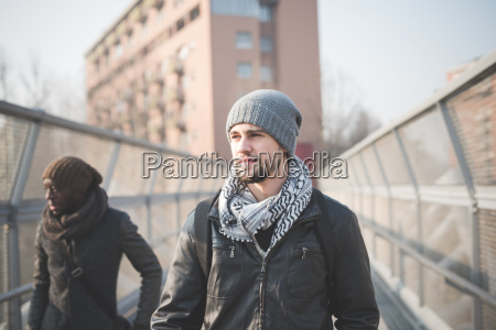 two young men strolling on footbridge