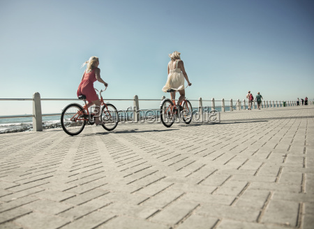 young women cycling on seafront cape