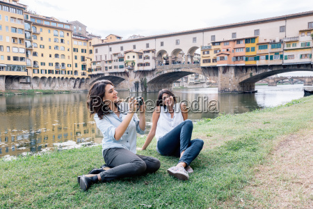 lesbian couple sitting on arno river