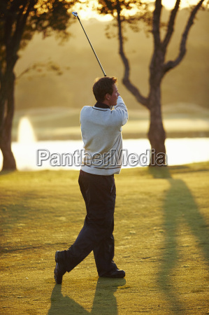 golfer in sunlight holding golf club