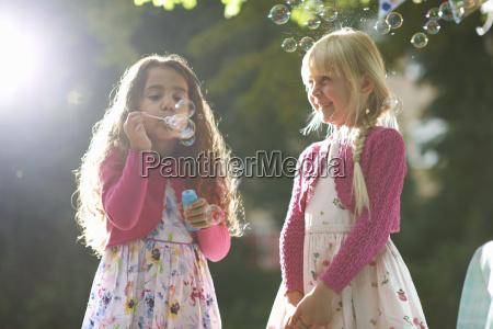 two cute girls blowing bubbles in