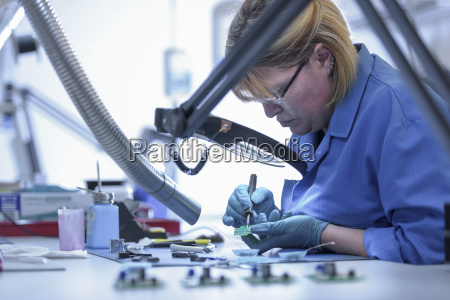 female worker assembling electronics in electronics