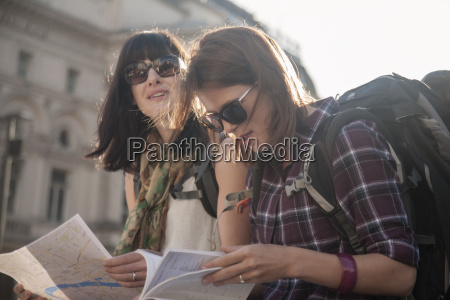 two women backpackers sitting in sunlight