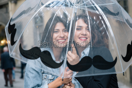 lesbian couple underneath transparent umbrella looking