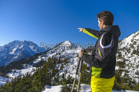 side view of skier pointing at