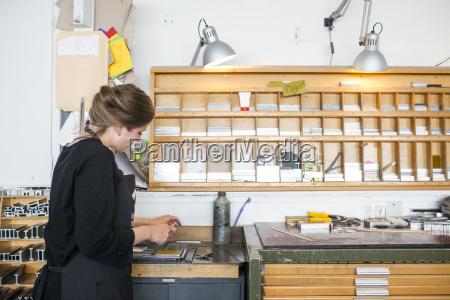 female printer selecting letterpress letters in