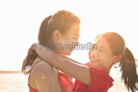 mid adult woman and daughter hugging