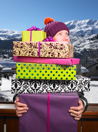 young woman holding pile of presents