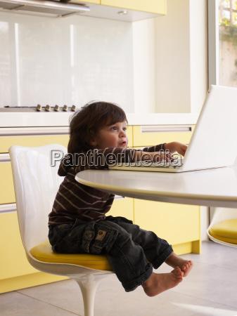 boy using laptop in kitchen