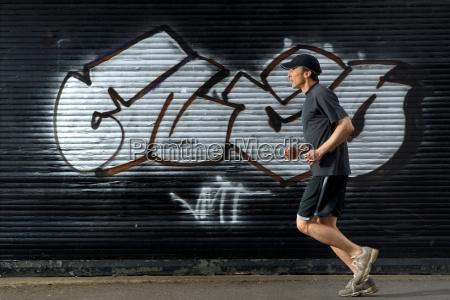 male runner passing graffiti in street