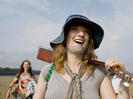 woman walking with guitar on shoulder