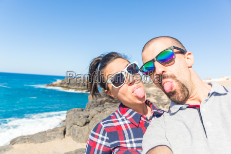 young couple sticking out tongues for