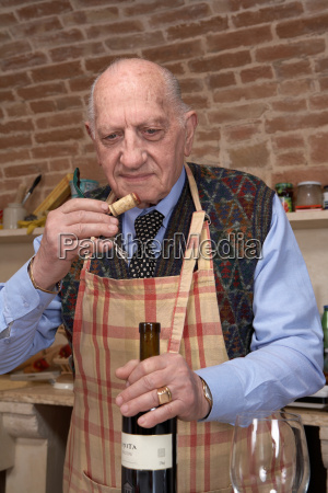 senior adult man sniffing wine cork