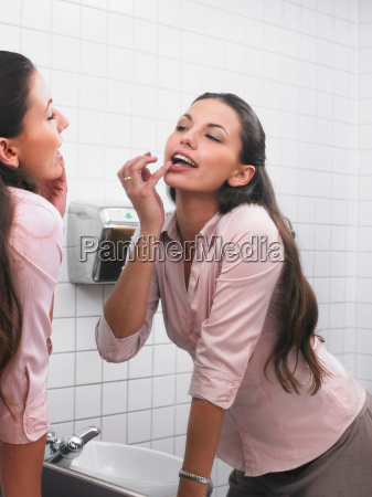 woman, reflected, in, office, washroom, mirror - 18415094