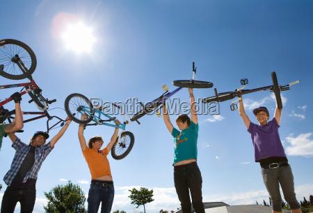 teen boys lifting bikes in air