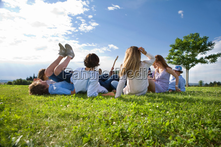 teen group laying on grass in
