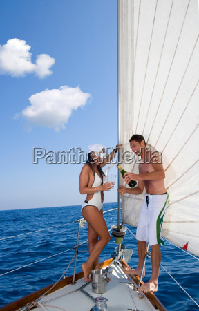 couple drinking champagne sailboat