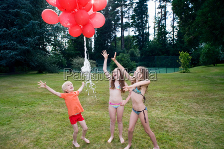 kids letting go red balloons