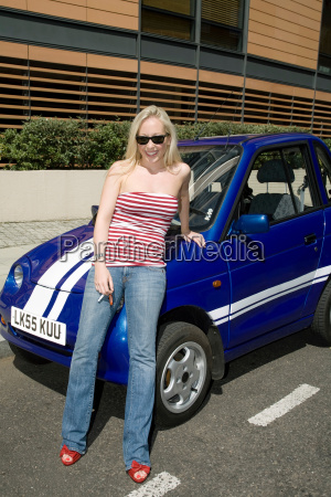young woman leaning on electric car