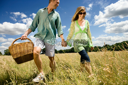couple with picnic basket in field