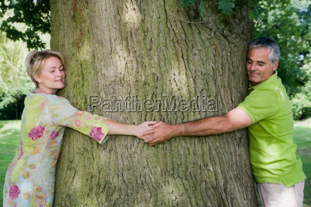 couple hugging a tree close up