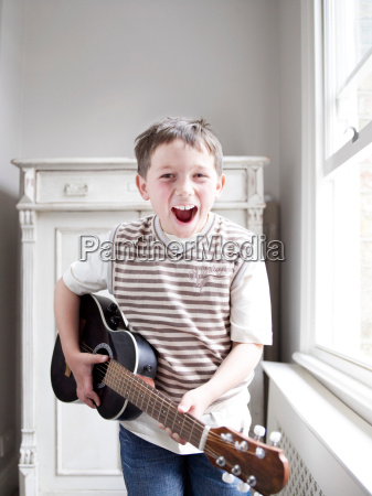 young boy standing playing guitar