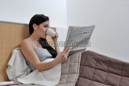 woman reading paper in her bed