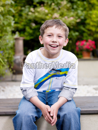 young boy sitting outside on patio