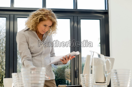 woman looking at papers and computer