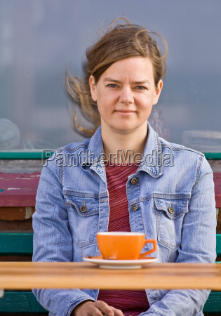 woman sitting at a cafe drinking