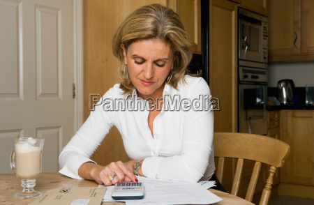 woman using calculator at kitchen table