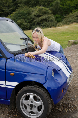 young woman washing electric car