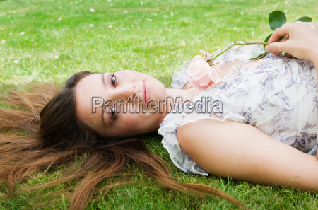 woman laying on grass holding rose