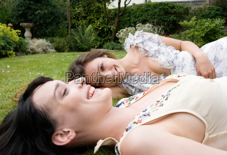 2 women laughing laying on grass