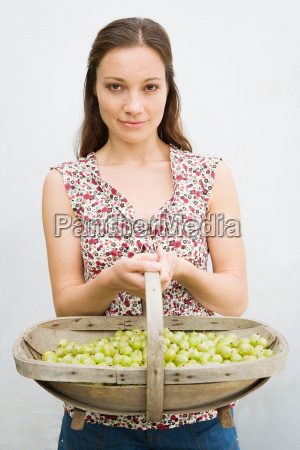 woman holding basket with berries