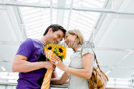 couple smiling exchanging flowers