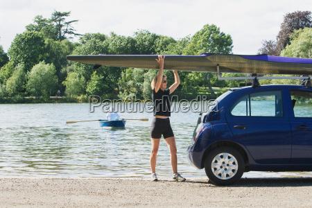 woman lifting canoe off car