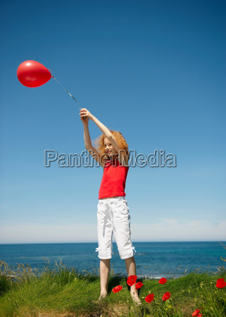 young girl standing with red balloon